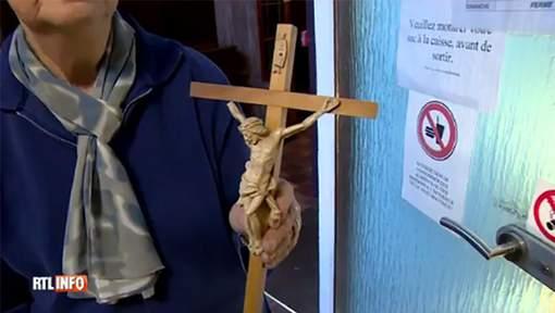 Una mujer belga protesta contra la decisión de Cruz Roja de retirar las cruces.