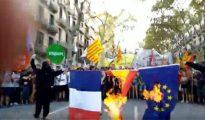 Catalanes queman las banderas de Francia, España y la Unión Europea.