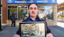 El comerciante José Luis Muñoz, delante de su tienda ya rotulada como «Mundo textil» sostiene una fotografía del establecimiento con su anterior nombre (ABC)