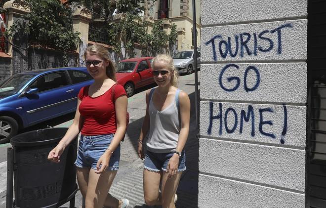 Dos turistas caminan junto a unas pintadas en la zona del Parque Güell.