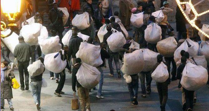 Un grupo de manteros, transportando material de venta en el centro de Barcelona