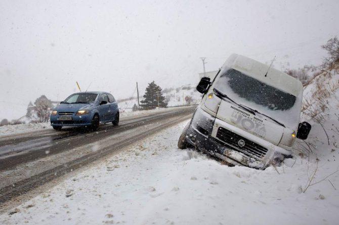 Un coche circula por una carretera del paso fronterizo del Portalet entre España y Francia cubierta por la nieve caída en la zona.