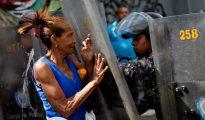 Una mujer se enfrenta a las fuerzas del orden durante una protesta por la falta de comida en Caracas