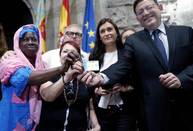 El presidente de la Generalidad, Ximo Puig (d) y la consellera de Sanidad, Carmen Montón, entre otros, muestran una de las tarjetas sanitarias tras la presentación del Plan de Universalización de la Sanidad en en 2015.