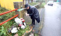 Una mujer deja flores en la nave donde hallaron el cadáver de Diana Quer