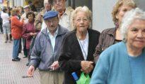 Pensionistas españoles hacen cola para cobrar.