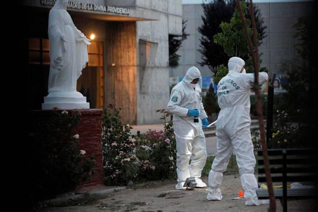 Agentes investigando los hechos junto a una iglesia de un vecindario de Chile.