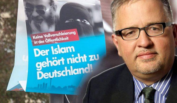 Arthur Wagner y un cartel de AfD contra laislamización de Alemania.