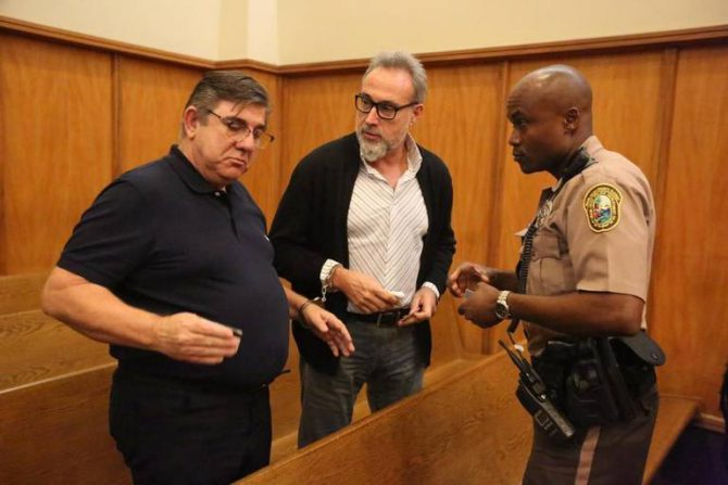 Luis Riu, en el centro, esposado tras su detención. MIAMI HERALD