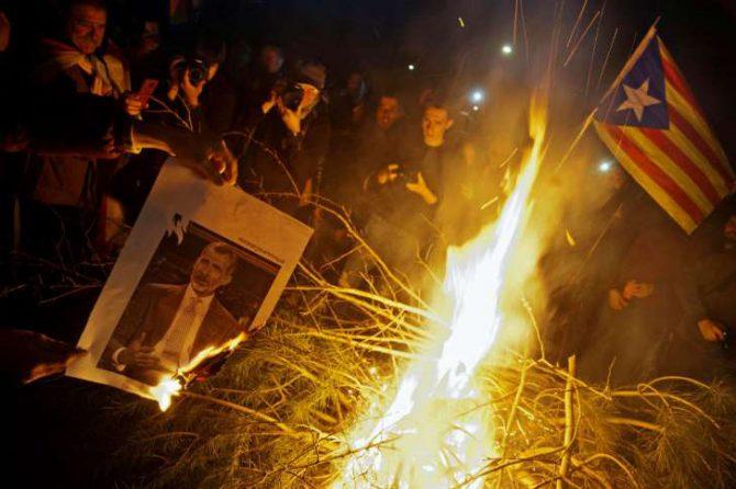 Manifestantes independentistas queman fotos del Rey durante los cortes del AP7