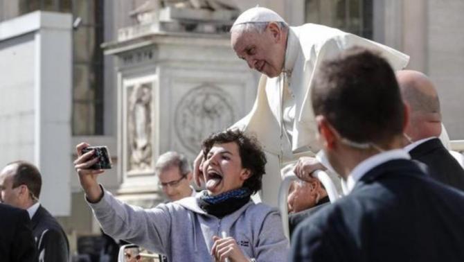 El Papa Francisco posa para un selfie con una joven a su llegada a la audiencia general de los miércoles en la plaza de San Pedro del Vaticano