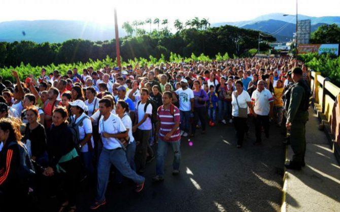 """Centenares de personas caminan por el puente fronterizo """"Simón Bolívar"""" entre Colombia y Venezuela."""