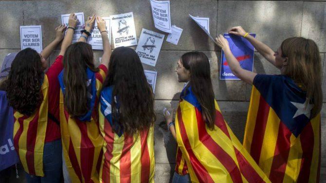 Menores de edad con esteladas cuelgan carteles a favor de votar en el referéndum