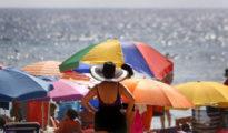 Varios turistas disfrutan del sol y el agua en la playa de Levante de Benidorm.