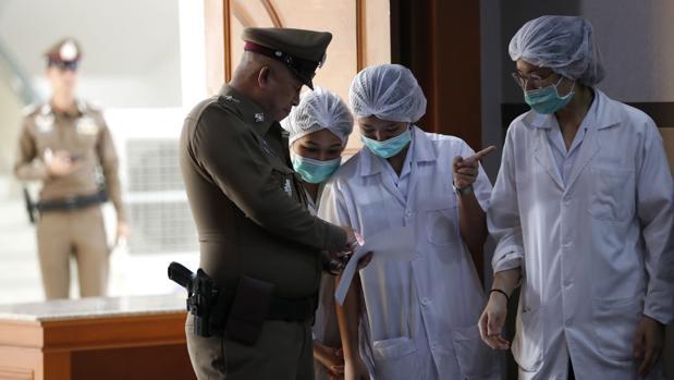 Personal del hospital tailandés y un oficial de policía durante la rueda prensa sobre la condición de los niños