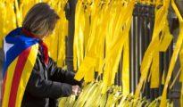 Una mujer coloca lazos amarillos en una verja.