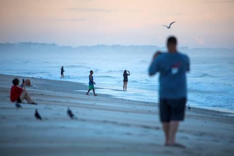 Varias personas toman fotografías al amanecer en una playa de Carolina del Norte.