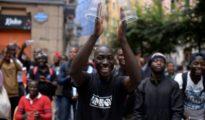 Inmigrantes africanos recién llegados a España bailan durante una fiesta de bienvenida organizada por grupos vecinales.