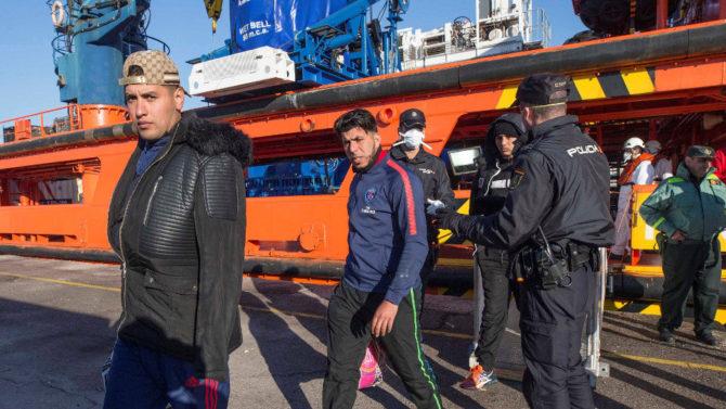 Agentes de policía nacional custodian el desembarco de 48 inmigrantes argelinos en Málaga.