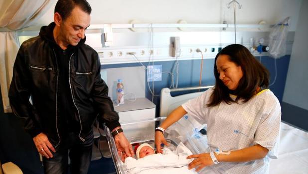 Karem y Joaquín miran a su hijo Derek, el primer madrileño nacido en 2018 en Madrid