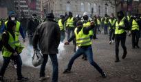 París, 8 de diciembre de 2018: un manifestante lanza un bote de gas lacrimógeno contra la policía durante una manifestación de los 'chalecos amarillos' en las inmediaciones del Arco del Triunfo.