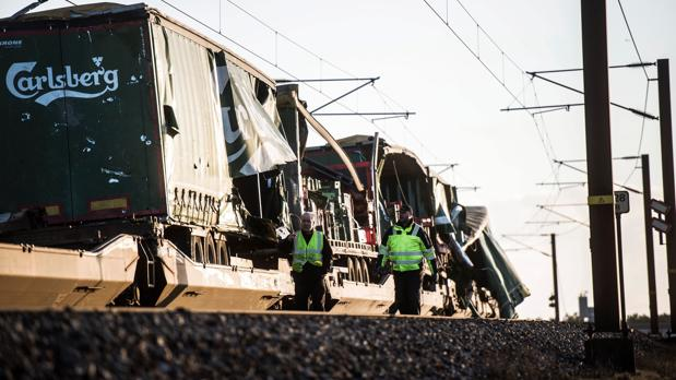 Varios operarios pasan junto un tren de carga en el puentoe Gran Belt en Nyborg (Dinamarca), tras registrarse el accidente ferroviario