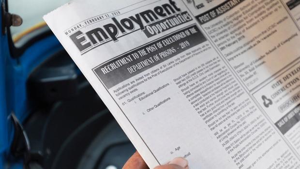 Un hombre lee el anuncio de la vacante de verdugos en un periódico local