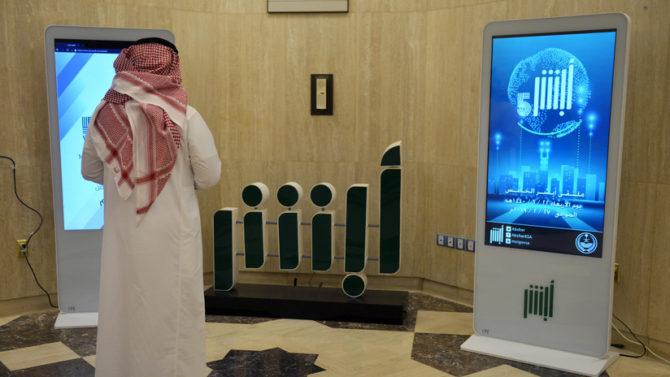 Un empleado del Ministerio del Interior del Gobierno saudí frente al logo de la aplicación Absher. Riad, Arabia Saudita. 19 de febrero de 2019 (RT)