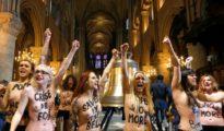 Feministas semidesnudas en el interior de una iglesia.