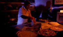 Un cocinero hace pizza iluminado por velas en Caracas