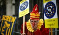 Un partidario de la UE vestido de bufón junto a un cartel de manifestantes anti-UE