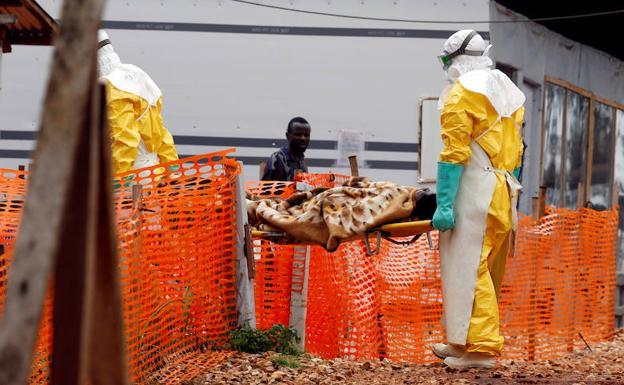 Dos sanitarios portan a un enfermo de ébola, en un centro de la República Democrática del Congo