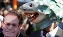 Un manifestante exhibe una máscara de tiburón mientras que otro porta una máscara del alcalde de Berlín, Michael Mueller, en la protesta contra el encarecimiento de la vivienda en Berlín