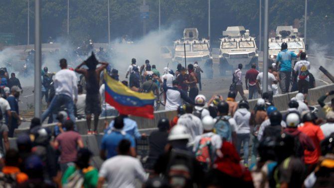 Grupos de manifestantes se enfrentan a las tanquetas de las fuerzas bolivarianas en la proximidades de la base aérea de La Carlota