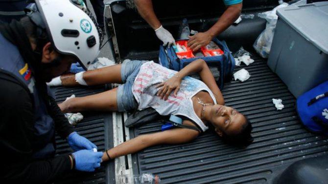 Una joven recibe asistencia tras ser herida por las fuerzas de Maduro
